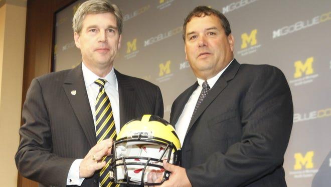 Michigan athletic director Dave Brandon, left, poses with football coach Brady Hoke on Jan. 12,  2011.