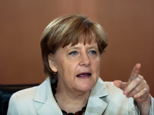 German Chancellor Angela Merkel points at a cabinet member as she leads the weekly cabinet meeting at the chancellery in Berlin, Germany, Wednesday, May 14, 2014.  (AP Photo/Markus Schreiber)