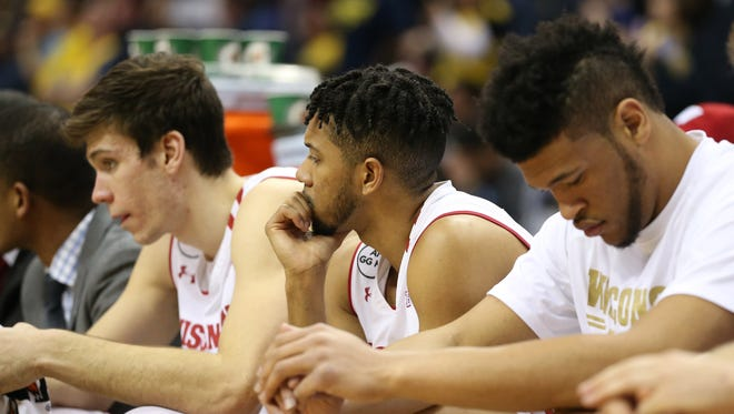 A dejected  Jordan Hill (center)  watches the final moments of Wisconsin's Big Ten Championship loss on Sunday.