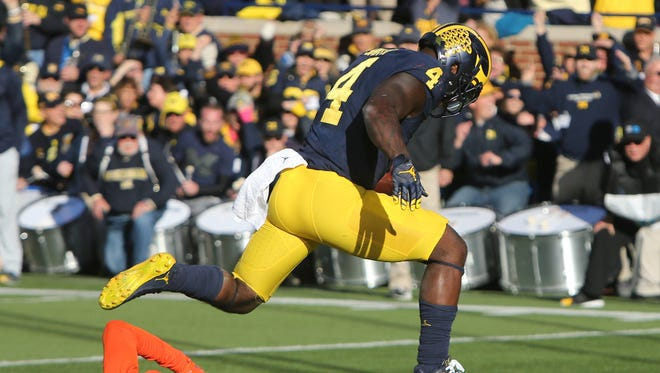 Michigan's De'Veon Smith goes over Illinois' Stanley Green for a touchdown during U-M's 41-8 win Saturday at Michigan Stadium.
