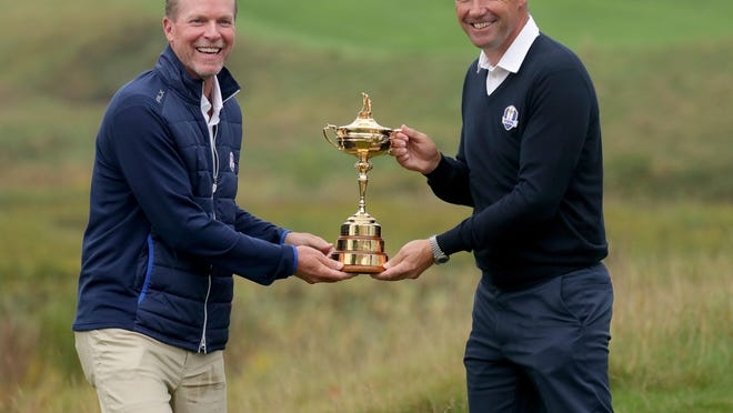 Steve Stricker, left, 2020 Ryder Cup U.S. team captain and Padraig Harrington, 2020 Ryder Cup European team captain, share a laugh as they hold the Ryder Cup trophy after the 2020 Ryder Cup Year-to-Go press conference in 2019.