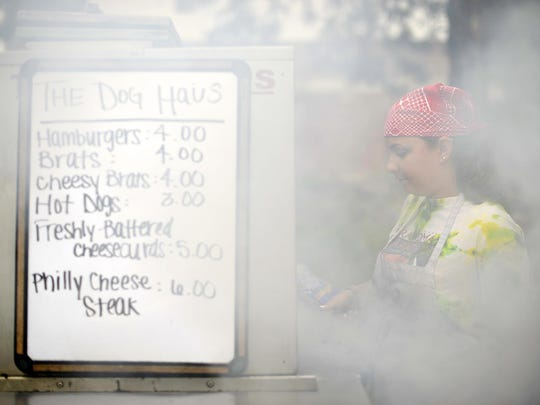 Hope Coppens, with The Dog Haus, cooks food during the Food Truck Friday event last week in downtown Green Bay. The event is put on by On Broadway.