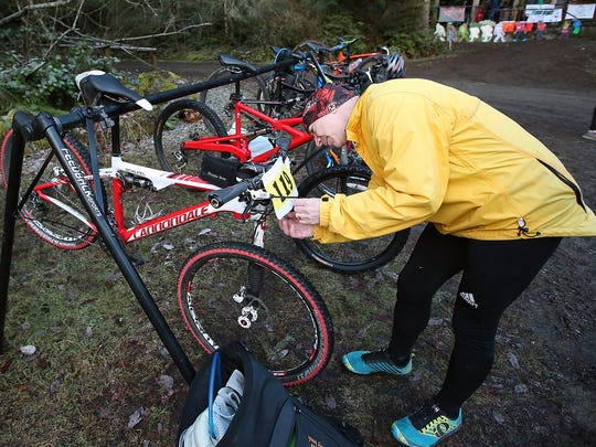 Greg Pelton of Silverdale attaches his bib number to his bike Saturday prior to the start of the Green Monster Duathlon on Green Mountain.