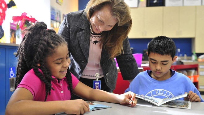 In this file photo, reading teacher Brenda Pollock works with fourth-graders Amaya Barnes and Ramesh Sarki, both 10, at A.Z. Kelley Elementary School. Reading teacher Brenda Pollock works with fourth-graders Amaya Barnes and Ramesh Sarki, both 10, at A.Z. Kelley Elementary School.