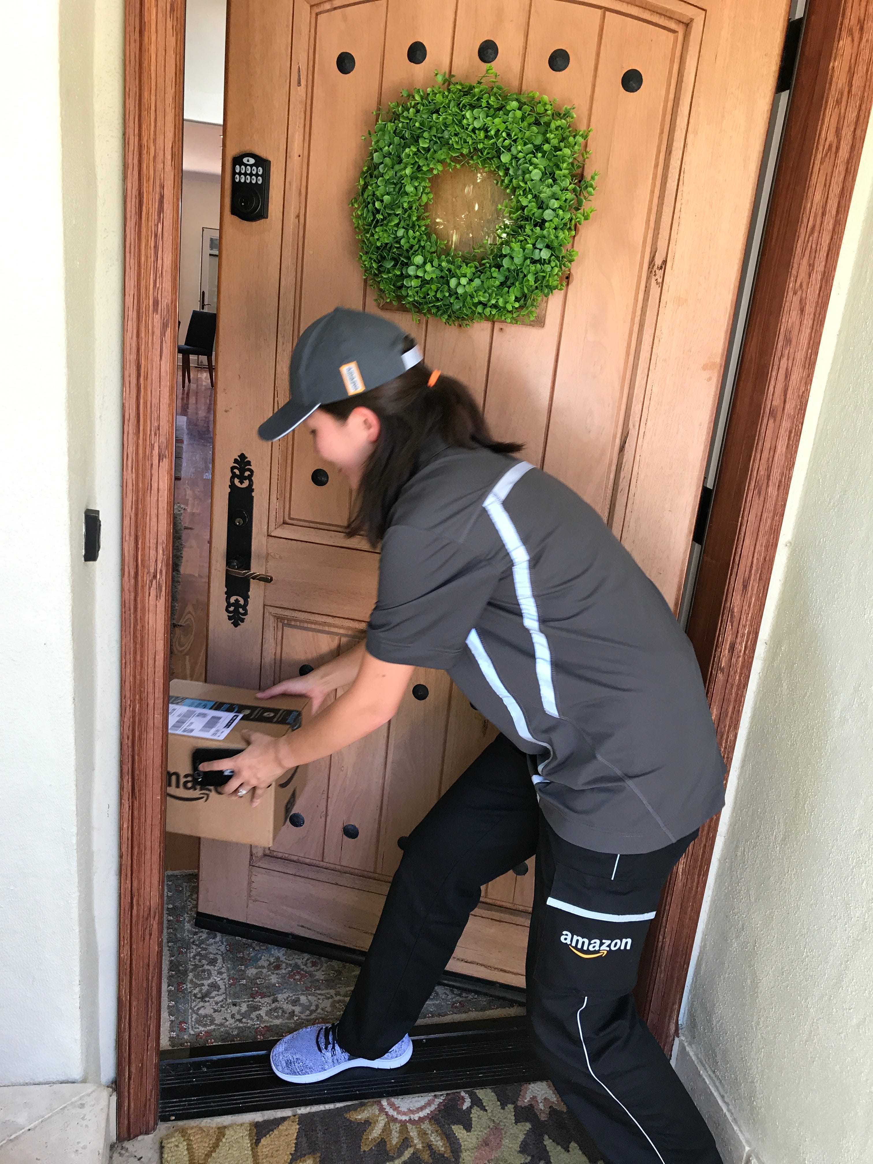 An Amazon Logistics delivery person places a package inside the front door of a customer after having the smart lock on the door opened by the Amazon Key ... & Amazon Key delivery service lets driver leave packages inside the door Pezcame.Com