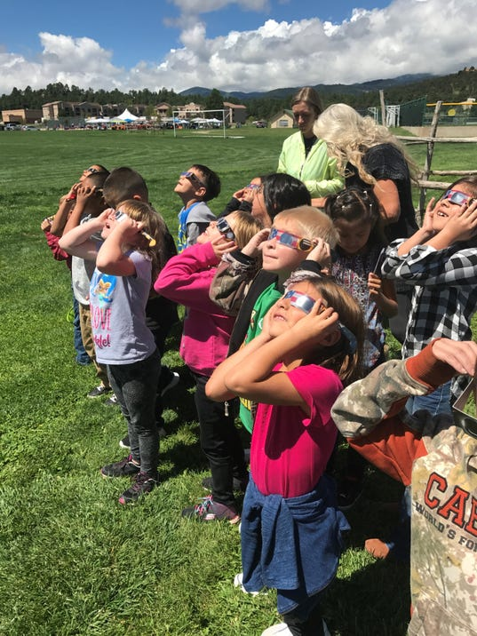 Ruidoso Students watching the recent solar eclipse with NASA approved glasses and viewers made by parents and students. They were able to learn about the scale size of the earth, moon, and sun.