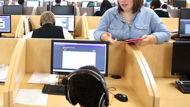 Lindsay Herrmann, Carpe Diem English teacher, talks with students in the learning center at Carpe Diem-Aiken in College Hill Thursday, October 1, 2015. Herrmann spends half of her day in the learning center assisting students with their independent computer work and the other half of her day working with students on English projects.