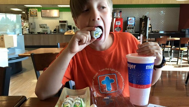 Fletcher Moore eats sushi at a Meijer store in Grand Rapids. The 9-year-old had a party and spent nine hours at the store to celebrate his birthday.