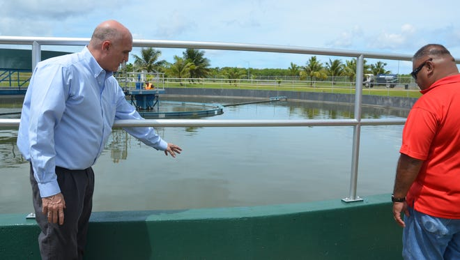 In this September 2013 file photo, Martin Roush, left, Guam Waterworks Authority general manager, explains how wastewater is treated at the Northern Wastewater Treatment plant. The water agency spent $10 million to allow the plant to give primary treatment to sewage, which had been pumped out to sea, untreated. The next step, using military funding, is to add secondary treatment, which uses bacteria to further break down the waste.