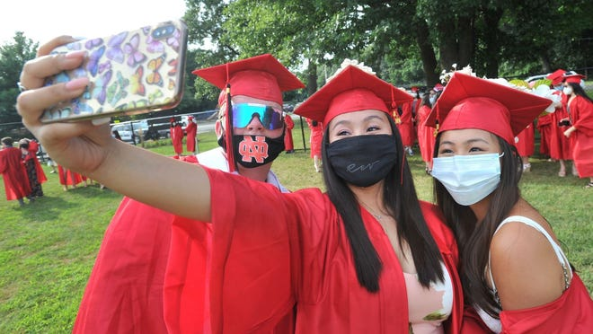 From left, Michael Levine, Daisy Tran and Erin Leung take a picture during the North Quincy High School graduation at Veterans Stadium in Quincy, Friday, July 24, 2020. Tom Gorman/For The Patriot Ledger