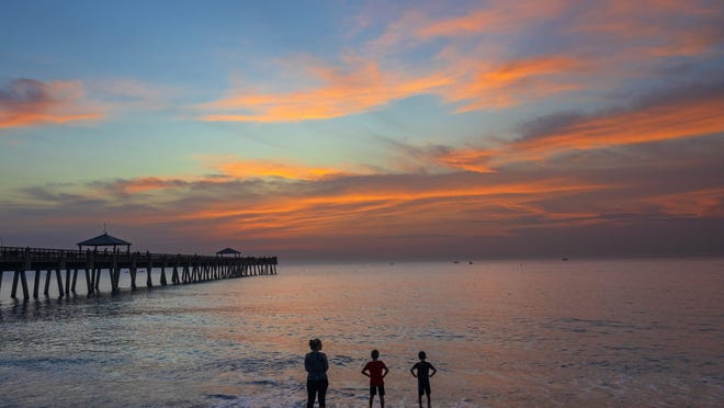 "Christina Caldovino and her sons Robbie, 10, and Nickie, 8, watch sunrise at the Juno Beach Pier on May 18, the first day the pier and Palm Beach County beaches were open again. ""We are big time beach-goers, so we were really looking forward to being back on the first day to see the sunrise,"" said Caldovino, of Royal Palm Beach."