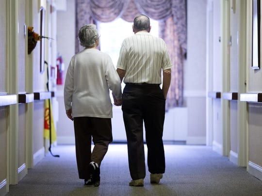 An elderly couple walks down a hall of a nursing home in Easton, Northampton County, in 2015.