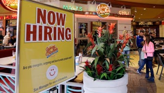 A restaurant posts a sign indicating they are hiring, in Miami. Fewer Americans signed up for unemployment benefits last week, another sign the U.S. job market remains healthy.