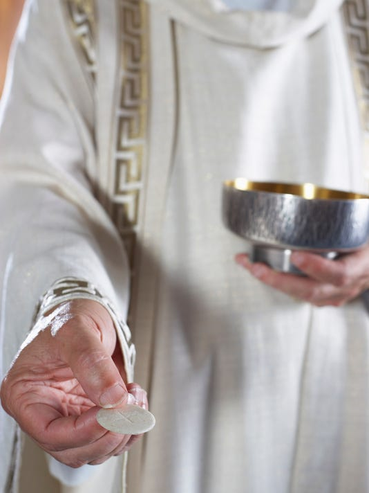 Priest with Communion wafer and chalice