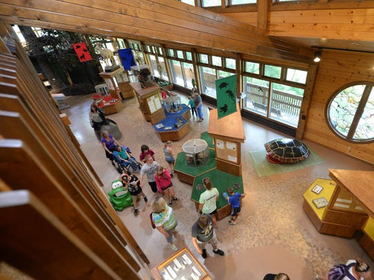 Visitors walk through the main level of the Nature Center at Bay Beach Wildlife Sanctuary viewed from the upper level on Thursday, July 9, 2015.
