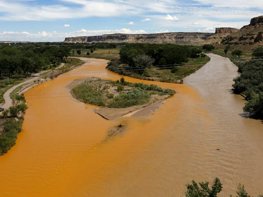The confluence of the Animas River, at left, and the San Juan River, right, is pictured Aug. 8 as a plume of orange water contaminated with mine waste flows through Farmington after the Gold King Mine spill.