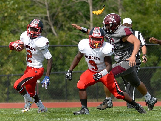 Wilson's Rickey Gamble Jr., left, turns the corner eluding Greece Arcadia;s Chuck Finoccharino, right, as a penalty flag flies for offensive holding on the play during the season opener at Greece Arcadia High School on Saturday, Sept. 2, 2017. Wilson beat Greece Arcadia 36-2.