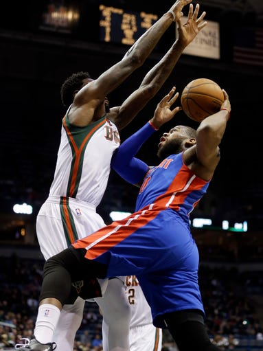 Detroit Pistons' Greg Monroe, right, tries to shoot
