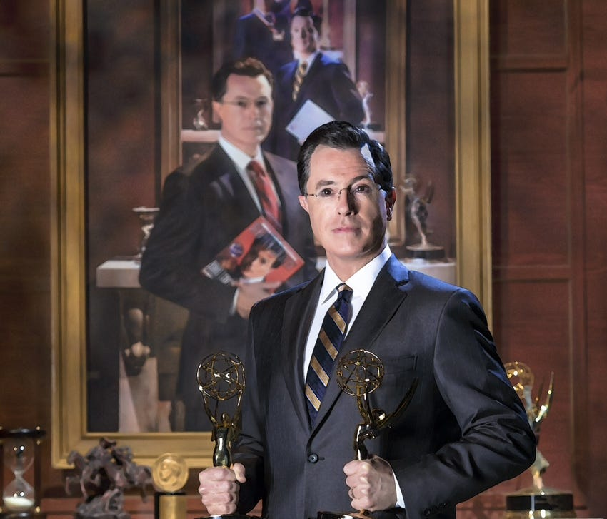 This handout photo provided by the Smithsonian shows Stephen Colbert poising in front of his portrait.