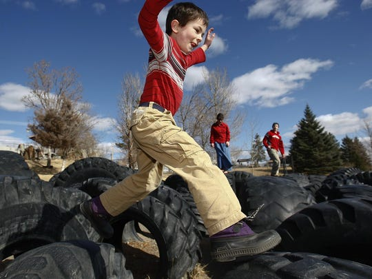 Levi DuPaul, 6, jumps from tire to tire at Art Higgins