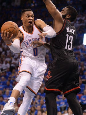 Oklahoma City Thunder guard Russell Westbrook drives to the basket in front of Houston Rockets guard James Harden.