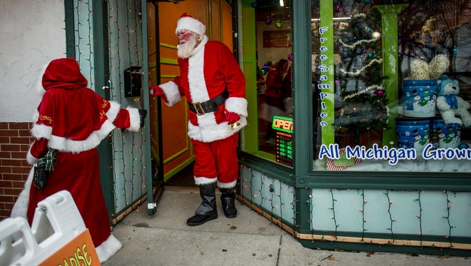 Santa and Mrs. Claus walk down the street after visiting Popcorn Paradise during the 2016 Merrytime Christmas event Saturday in Marine City.