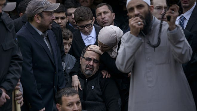 Namee Barakat, the father of Deah Shaddy Barakat, is comforted by his daughter Suzanne Barakat as they listen to a funeral prayer after his son was buried on Feb. 12, 2015, in Wendell, N.C.