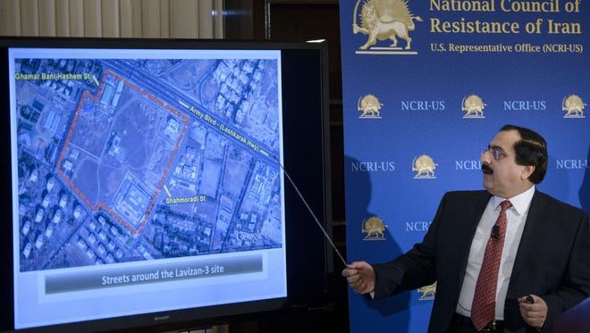 Alireza Jafarzadeh, U.S. representative of the National Council of Resistance of Iran, shows satellite photos during a news conference Feb. 24 at the National Press Club in Washington. NCRI says there is a secret nuclear enrichment site near Tehran.