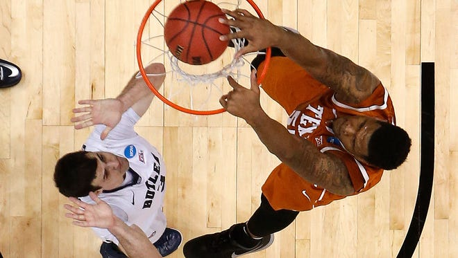 Texas' Cameron Ridley, right, dunks in front of Butler's Alex Barlow during the first half of an NCAA college basketball second round game in Pittsburgh, Thursday, March 19, 2015.  Butler won 56-48. (AP Photo/Gene J. Puskar)