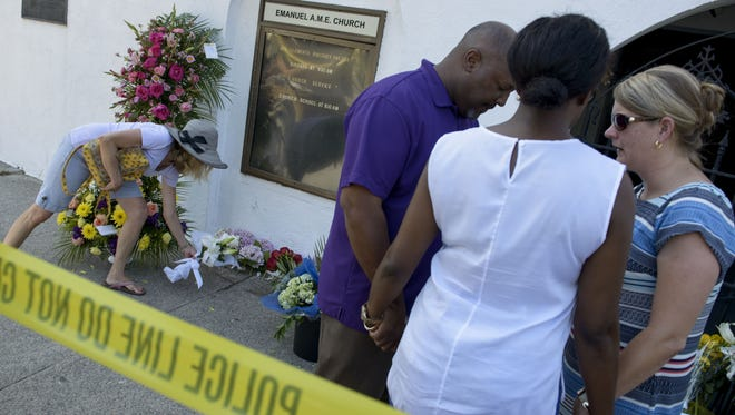 A woman places flowers as mourners pray at a makeshift memorial outside the Emanuel AME Church in Charleston on June 18, 2015.