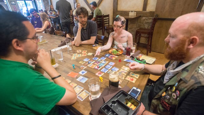 From left to right, Adam Robertson, Gilbert Podell-Blume, Victoria Wilson and Sean Snow play a game called Forbidden Island at Dungeons and Drafts, located at 1624 S. Lemay Ave., Unit 6, on opening weekend.