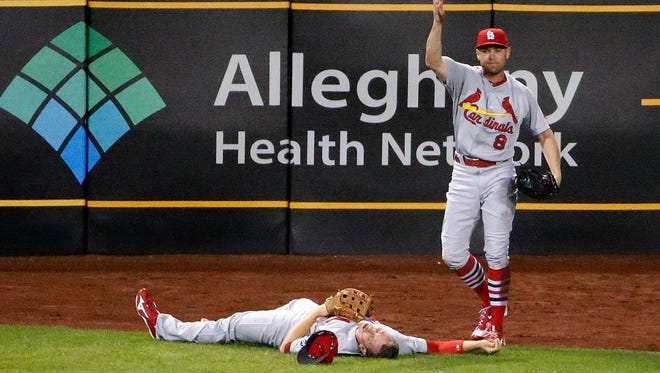 St. Louis Cardinals center fielder Peter Bourjos (8) calls for help after colliding with St. Louis Cardinals left fielder Stephen Piscotty while catching a fly ball by Pittsburgh Pirates' Josh Harrison in the seventh inning of a baseball game in Pittsburgh.