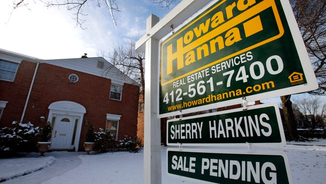 File photo taken in 2014 shows a for sale sign in front of a house in Mount Lebanon, Pa