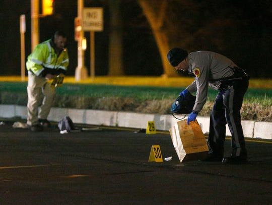 Police collect evidence at the scene of a fatal pedestrian