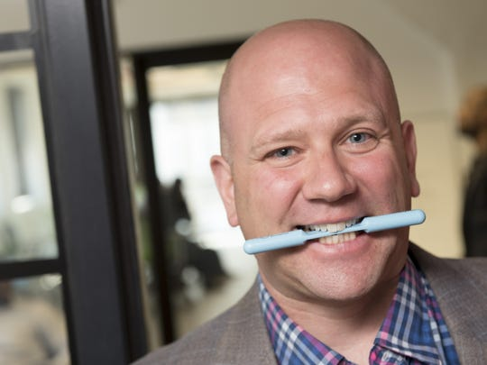 Matt Loria, shows off his product, the Smile Stick, a device designed to improve the user's mood and release endorphins in the brain by positioning the mouth into a smile.
