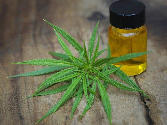 A vial of cannabidiol oil next to a hemp leaf on a table.