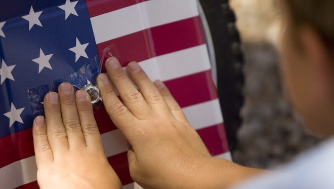 """Six-year-old Tommy Billings tapes an American flag paper plate to the wheel of his bike Monday, June 28, 2010 in preparation for Ahwatukee's """"Red, White and Boom"""" Independence Day celebration Saturday, July 3."""