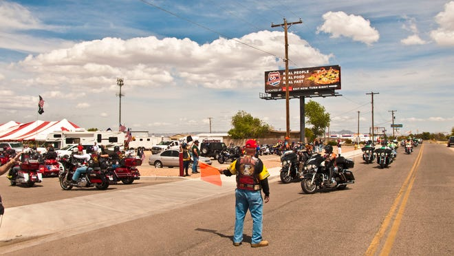 A man directs some motorcycle riders into the lot of Mother Road Harley-Davidson.