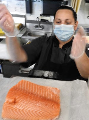Angler co-owner Tracy Girard-Simone weighs salmon from Norway.