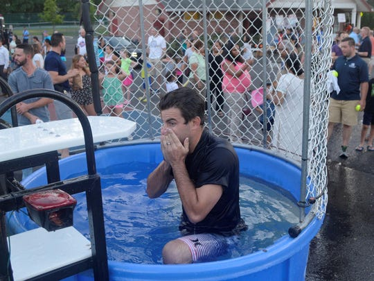 Patrolman Mike Rusin of the Fanwood Police wipes the water from his face after getting dunked by a youngster in the dunk tank at the National Night Out event in Fanwood on Tuesday, Aug. 4. It was the first year for the dunk tank at the event.
