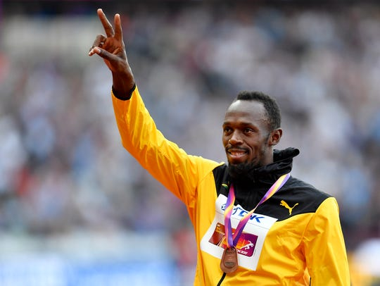 Bronze medalist Jamaica's Usain Bolt waves from the
