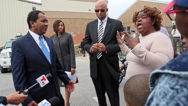 Dorothy Mangrum, grandmother of 19-year-old Raekwon Mangrum who was shot and killed on the 200 block of North Monroe Street on April 4, expresses anger with Mayor Dennis P. Williams while he made a stop on her street. Williams was handing out flyers trying to get more information or leads on recent shootings.