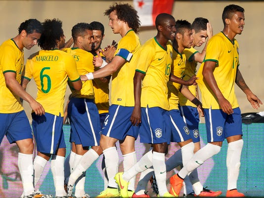 Brazil's Daniel Alves, third from left, celebrates with teammates after scoring against Panama during a friendly soccer match at the Serra Dourada stadium in Goiania, Brazil, Tuesday, June 3, 2014. Brazil is preparing for the World Cup soccer tournament that starts on June 12. Brazil won the match 4-0. (AP Photo/Andre Penner)