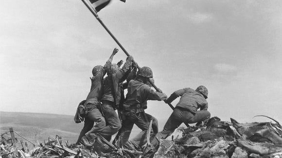 AP file photo FILE - This Feb. 23, 1945 file photo shows U.S. Marines of the 28th Regiment, 5th Division, raising the American flag atop Mt. Suribachi in Iwo Jima, Japan. Strategically located only 660 miles from Tokyo, the Pacific island became the site of one of the bloodiest, most famous battles of World War II against Japan. The photograph inspired a sculpture by Felix de Weldon which will be auctioned Feb. 22, 2013 in New York. (AP Photo/Joe Rosenthal, File)