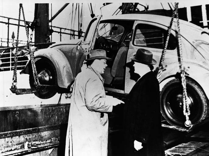 VW says this 1948 photo shows the first U.S.-bound Beetle being loaded onto a New York-bound ship in Rotterdam by Ben Pon, Sr. (left) a Dutch businessman. Other man is unidentified. It arrived in January 1949, one of two Beetles sold in the U.S. that year.