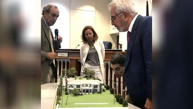 At a meeting of the Palm Beach Architectural Commission in 2017, members Maisie Grace, standing center, John David Corey and Bob Vila, far right, examine a model presented by architect Mark Marsh. Grace and Vila's terms on the board expire March 1.
