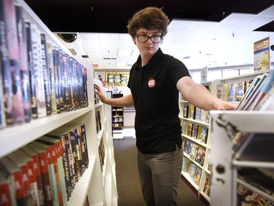 Eric Macaw puts DVDs on a shelf on July 15 at Cash Wise Video in Waite Park. He said working at the video store is a perfect summer job for someone his age.