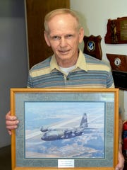 Retired U.S. Air Force Master Sgt. Carl Sellers, of Lebanon, holds a commemorative photo of a C-130 military transport aircraft signed by his fellow airmen upon his retirement in 1990.
