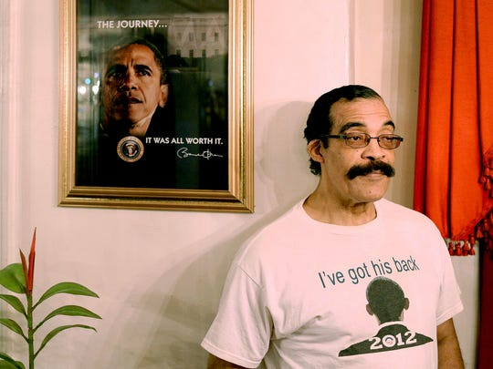 Thomas Wilson Jr. poses next to a framed photo of President