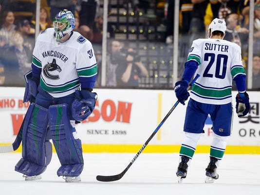 Vancouver Canucks' Anders Nilsson (31), of Sweden, skates off the ice past Brandon Sutter (20) after allowing four goals during the first period of an NHL hockey game against the Boston Bruins in Boston, Thursday, Oct. 19, 2017. (AP Photo/Michael Dwyer)